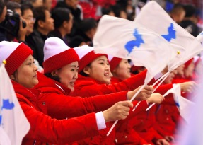 North Korea's cheerleaders hold the Unified Korea flag and cheer during the women's preliminary round ice hockey match between Switzerland and the Unified Korean team during the Pyeongchang 2018 Winter Olympic Games at the Kwandong Hockey Centre in Gangneung on February 10, 2018. / AFP PHOTO / Jung Yeon-je (Photo credit should read JUNG YEON-JE/AFP/Getty Images)